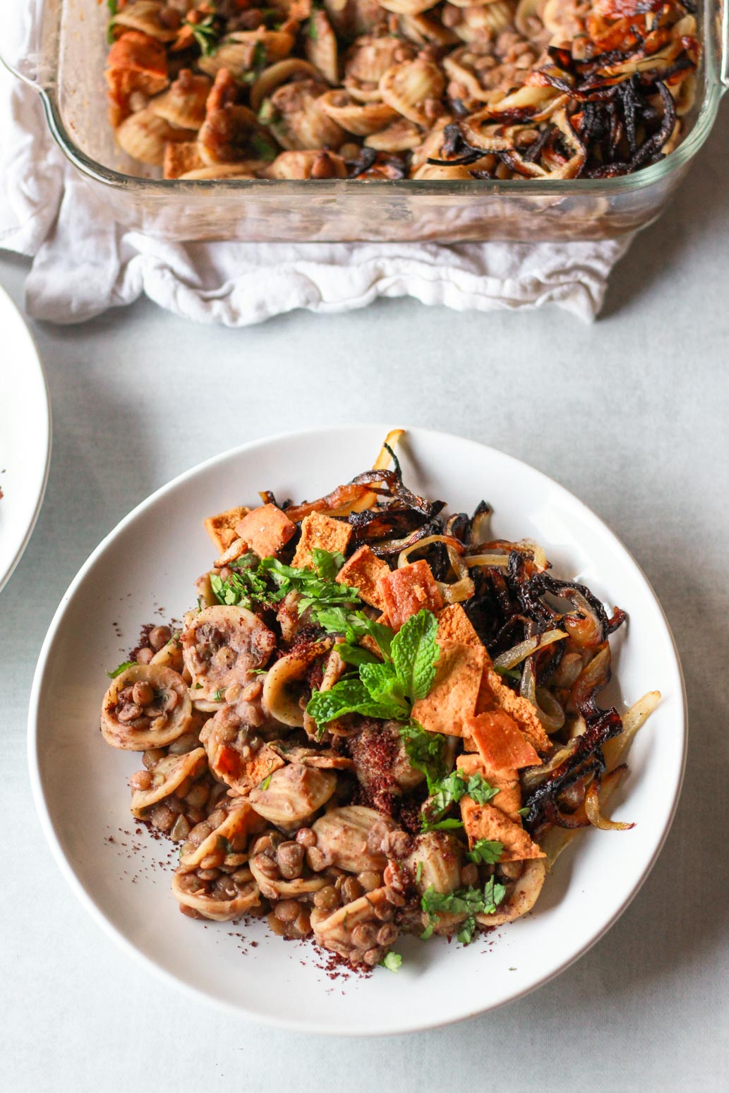 This Syrian pasta with lentils (horaa or horak osbao) is a great pantry friendly Middle Eastern comfort food. This vegan Mediterranean recipe is flavored with pomegranate molasses, sumac, and caramelized onions, and topped with crunchy pita chips.
