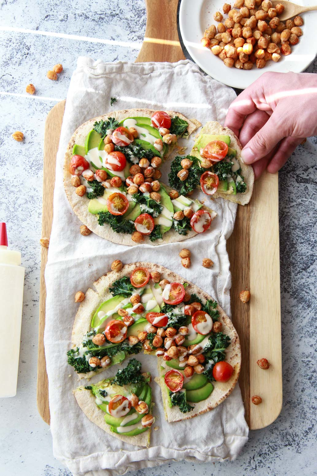 This avocado pita with spiced chickpeas and tahini puts a Mediterranean twist on avocado toast. This vegan recipe is topped with burst cherry tomatoes and massaged kale.