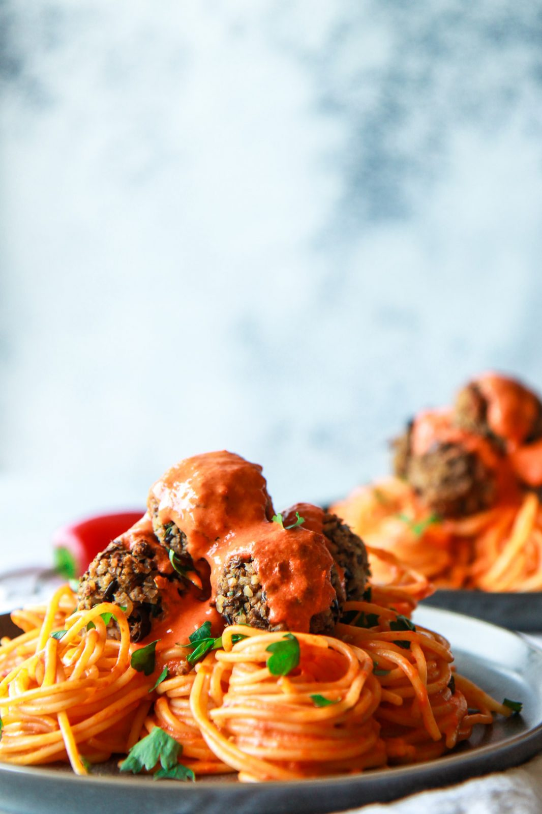 These eggplant meatballs are complemented with a roasted red pepper tahini sauce, served over pasta. Made with eggplants, walnuts, and parsley, these vegan meatballs are gluten-free with an oil-free option.