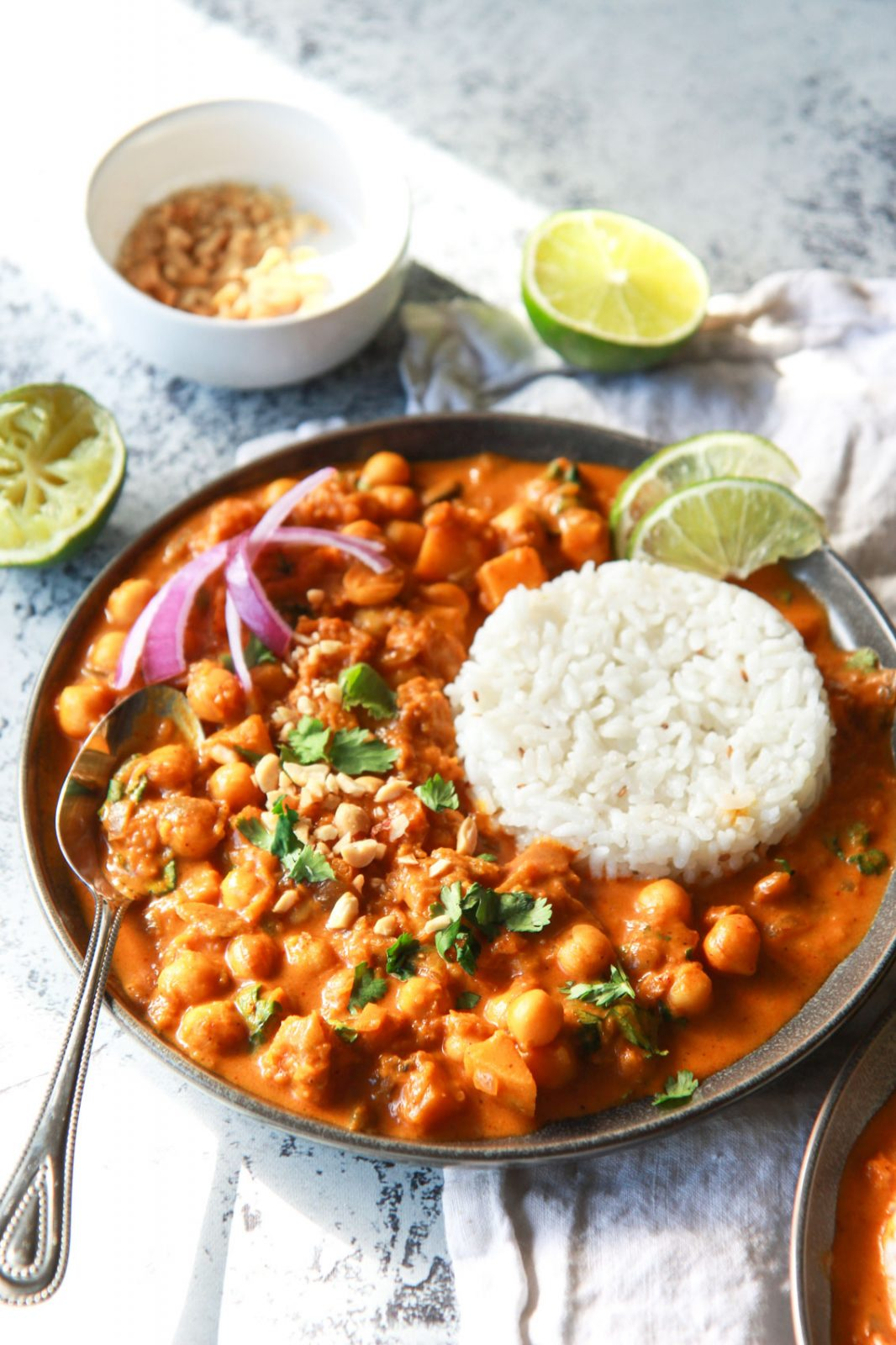 This vegan butternut squash & chickpea panang curry is a sweet, peanut flavored curry, inspired by the classic Thai dish. This vegan Thai peanut curry uses vegan panang curry paste, peanut butter, and coconut milk to create a rich and creamy base. This plant based curry uses chickpea and butternut squash instead of meat. Gluten-free with an oil-free option.