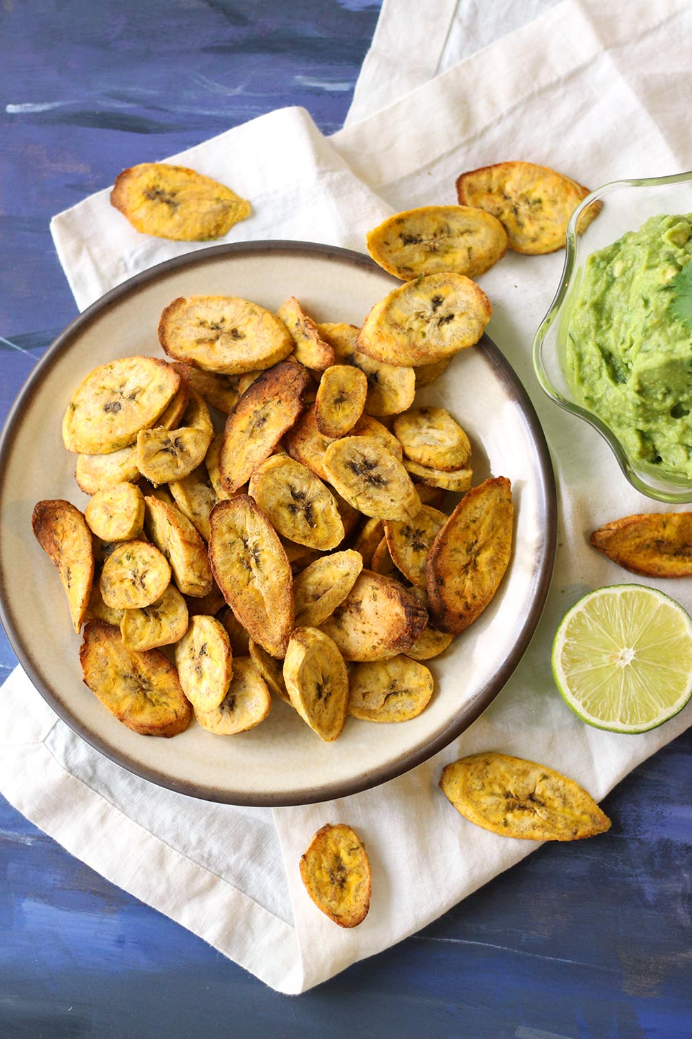 These air fryer plantain chips are a healthy vegan snack, served with creamy guacamole. The plantain chips are flavored with chili and lime, and can be baked in the oven as well. Gluten-free recipe.