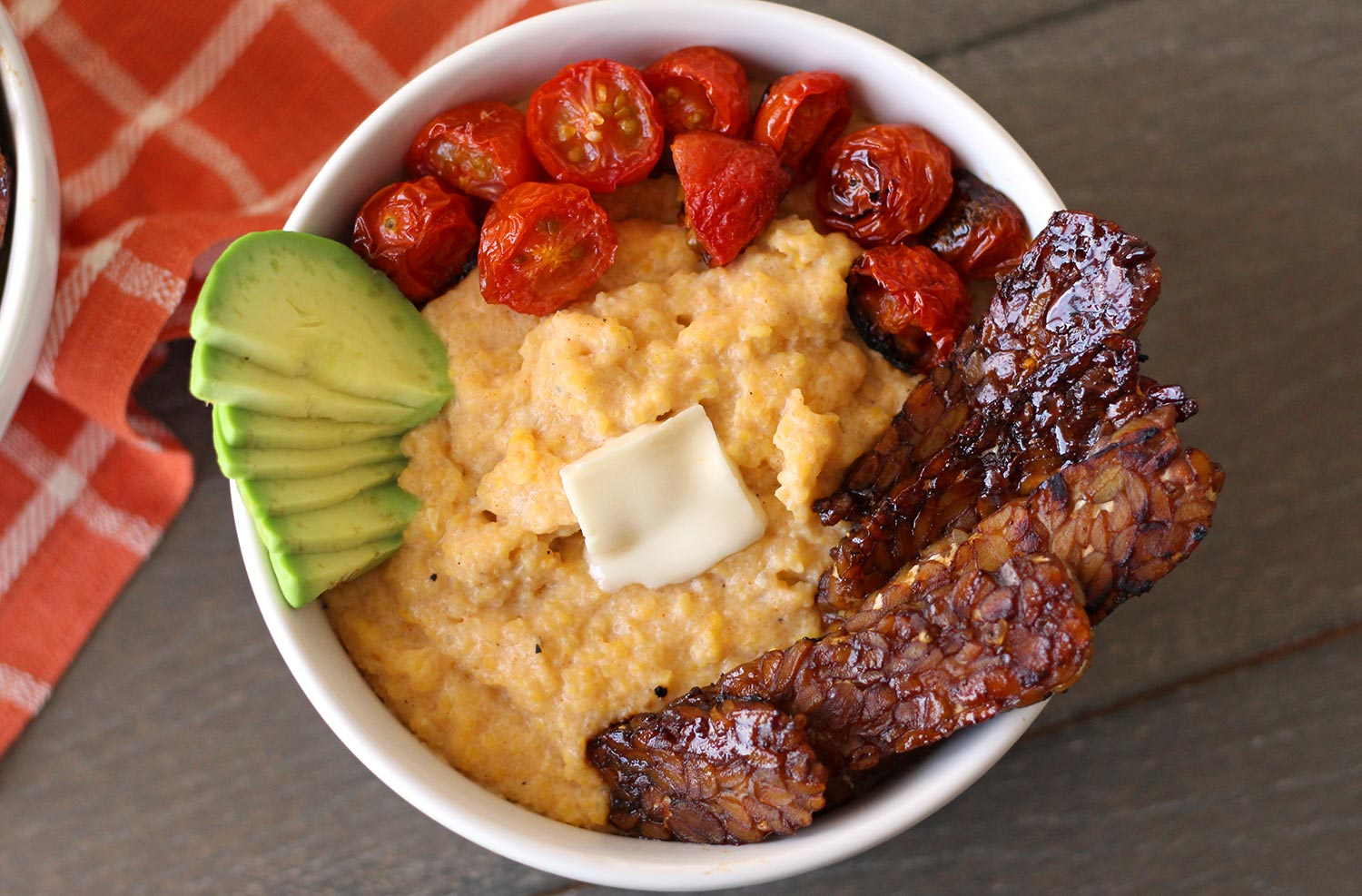 These creamy vegan grits are a delicious plant-based take on a Southern breakfast staple. Also gluten-free, these cheesy vegan grits recipe is topped with tempeh bacon and broiled tomatoes.