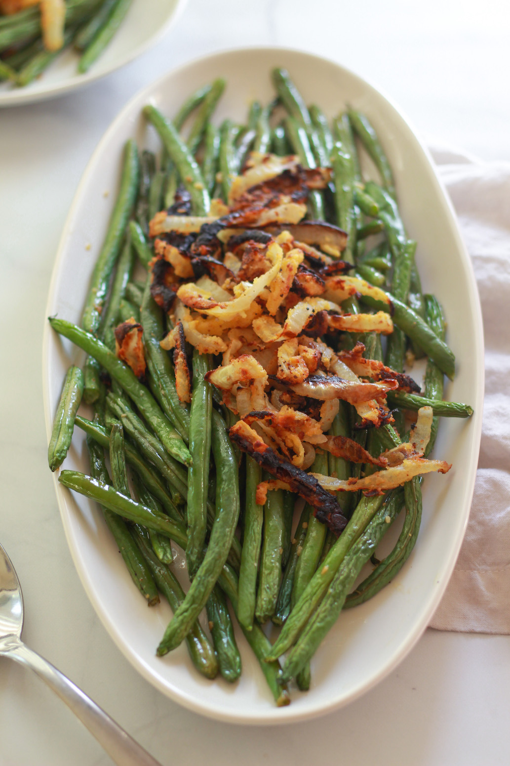 These lemon garlic green beans are simply roasted in the oven and topped with crispy chickpea fried onions. This is a simple vegan and gluten-free side dish recipe.