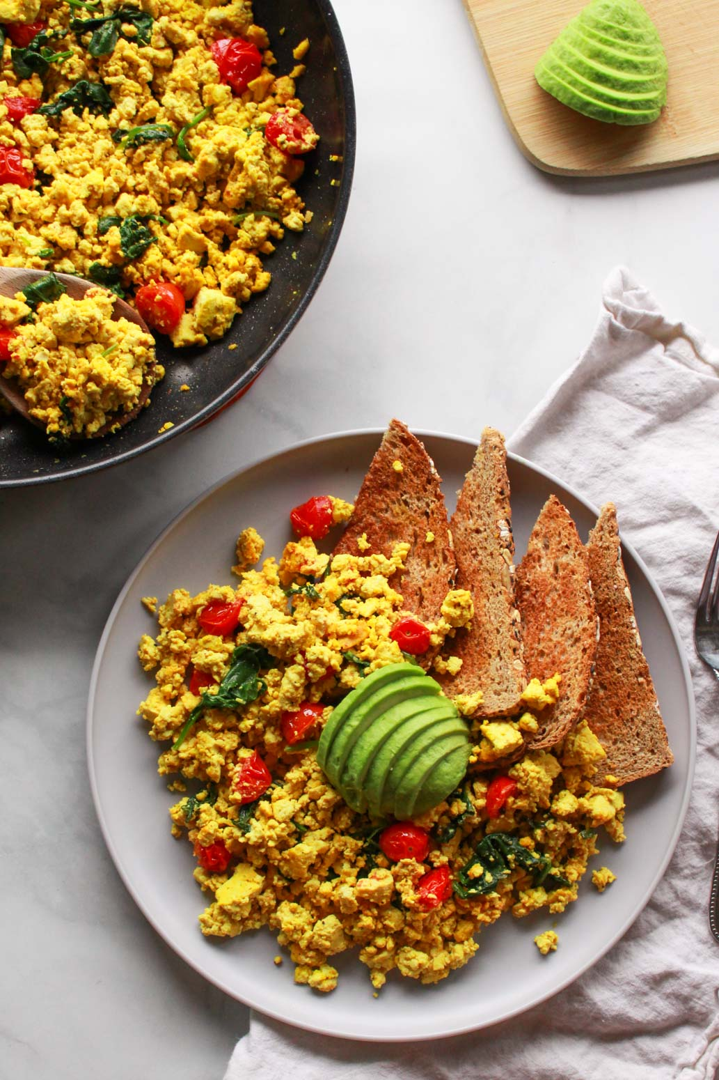 "How to make a super flavorful tofu scramble with spinach and cherry tomatoes. Forget about ""bland"" tofu, this tofu scramble is bursting with umami flavor, seasoned with nutritional yeast and tahini. A great plant-based alternative to scrambled eggs, this flavorful tofu scramble recipe is sure to be a vegan breakfast favorite!"