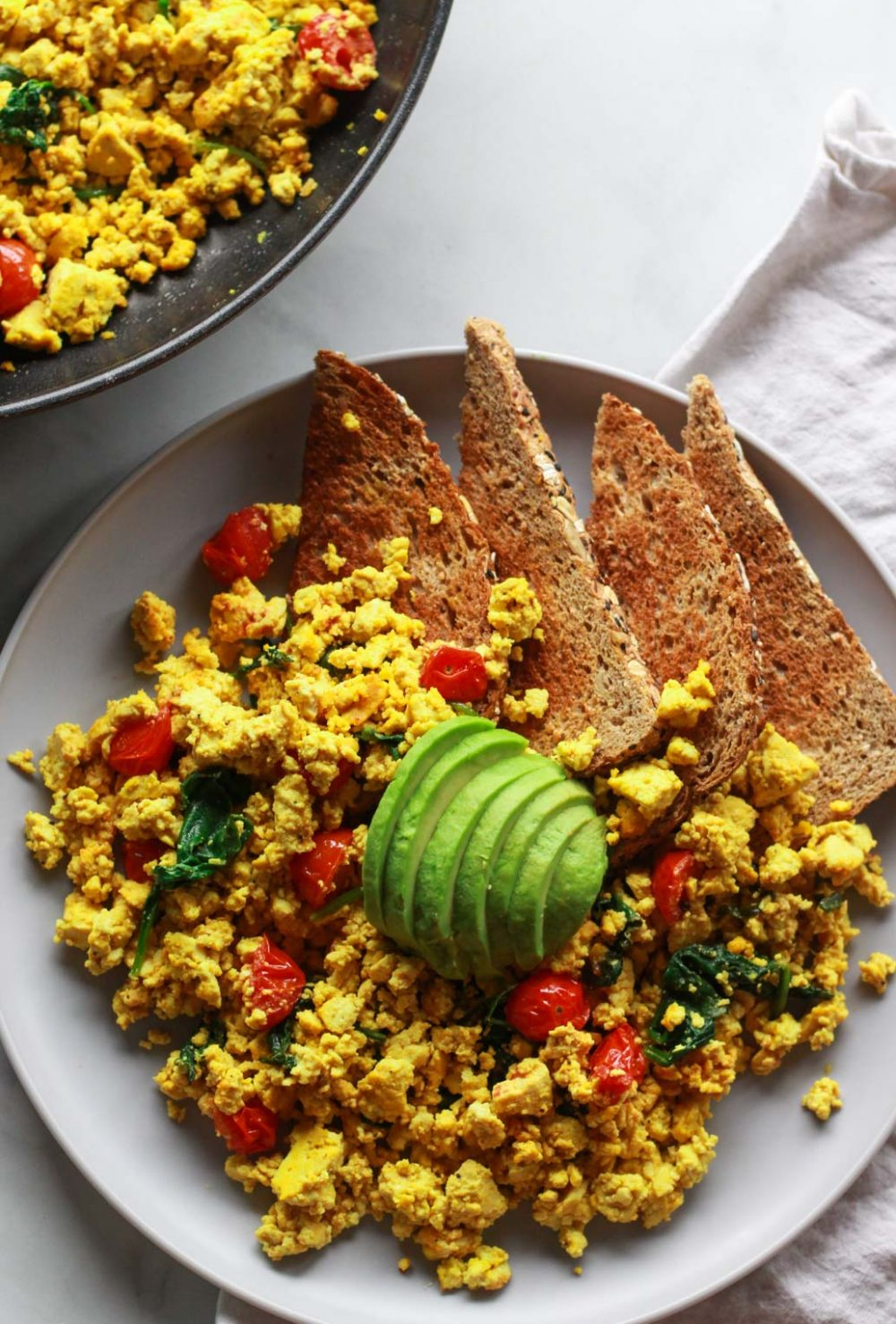 """How to make a super flavorful tofu scramble with spinach and cherry tomatoes. Forget about """"bland"""" tofu, this tofu scramble is bursting with umami flavor, seasoned with nutritional yeast and tahini. A great plant-based alternative to scrambled eggs, this flavorful tofu scramble recipe is sure to be a vegan breakfast favorite!"""