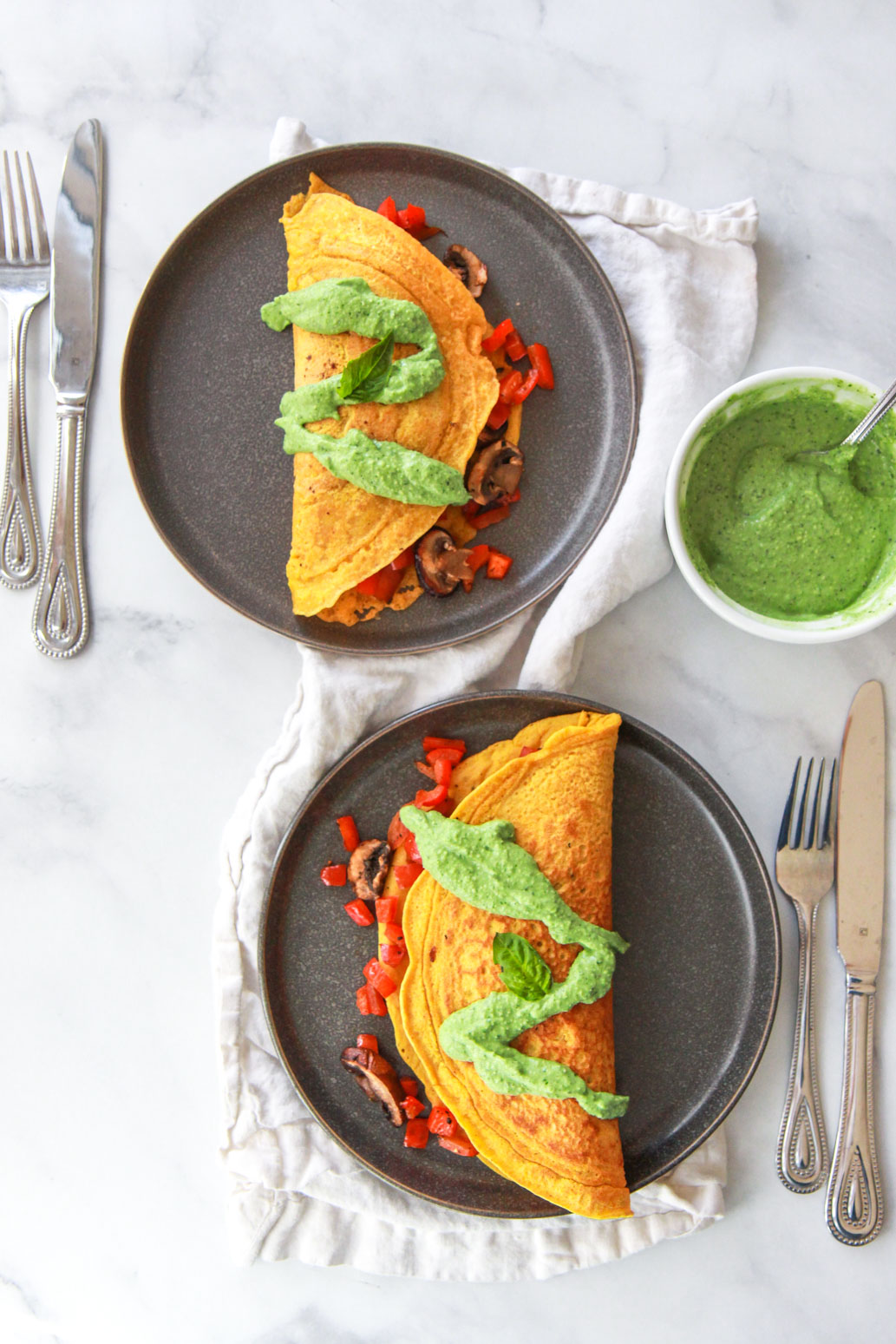 This chickpea omelet recipe is a delicious vegan alternative to a traditional egg omelet. Also gluten-free, this chickpea omelet does not crack or break when flipped, can be stuffed with your favorite veggies, and is topped with a dairy-free avocado pesto.
