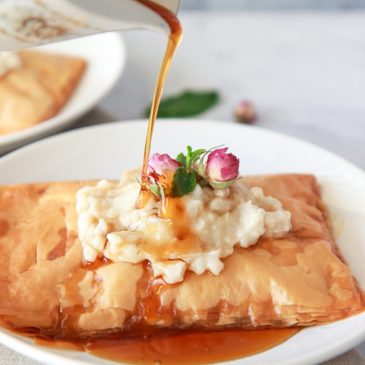This vegan Kahi with Geymar is an Iraqi pastry with a thick oat cream, topped with date syrup. This pastry is made up of layers of flaky phyllo dough, topped with vegan clotted cream, called Qaymar. Topped with date syrup or honey for a non-vegan option, this dessert is irresistible.
